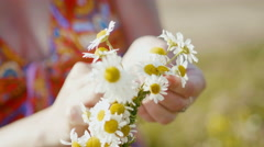 Woman in red dress collects a wreath of daisies in meadow of flowers, extremely Stock Footage