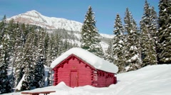 Close up of log cabin in the winter with snow covered mountains Stock Footage