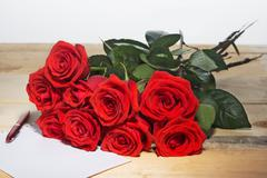 Bouquet of scarlet roses on a surface from wooden boards and the sheet of whi - stock photo