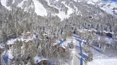 Drone video of ski lift above snow covered village 3 Stock Footage