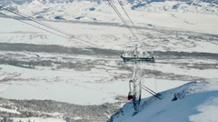 Ski lift rises over snow with mountains in background Stock Footage