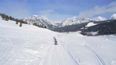 Drone shot of snowmobiles driving by mountains under blue sky 4 Stock Footage
