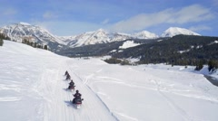 Drone shot of snowmobiles driving by mountains under blue sky 3 Stock Footage