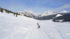Drone shot of snowmobiles driving by mountains under blue sky 2 Stock Footage