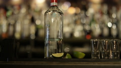 4K Barman pouring liquor into row of shot glasses Stock Footage