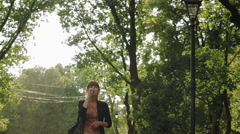 Girl elegantly smokes electronic cigarette walking  in the park - stock footage