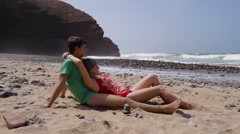 a young couple lying at the beach, legzira morocco africa - stock footage