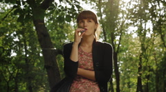 Girl elegantly smokes electronic cigarette in the sunny park Arkistovideo
