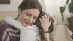 4K Daughter rushes into mother's arms at home and gives her a big hug. - stock footage