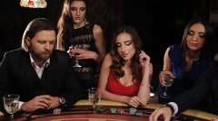 A group of young and beautiful people drinking champagne and playing blackjack - stock footage
