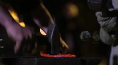 Blacksmith Forges Horseshoe. A blacksmith pounding a hammer on red-hot horseshoe Stock Footage