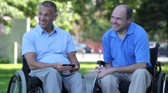 Two men in wheelchairs in a park. Stock Footage