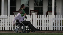 Man in a wheelchair with wife Stock Footage