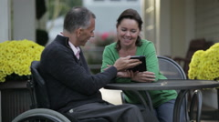 Man with spinal cord injury with his wife at a cafe Stock Footage