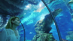 A woman looks at a lot of fish in the aquarium. It should be in the tunnel with - stock footage