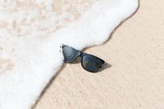 Black sunglasses on beach in water Stock Photos
