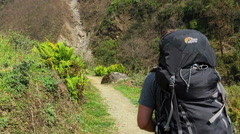 Hiker walking in mountain valley road. Himalayas Nepal travel nature HD video. Stock Footage