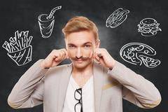 Handsome man and fast food temptation Stock Photos