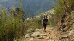 Tired hiker go up on the mountain road. Himalayas Nepal valley HD video. Stock Footage