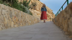 Romantic girl in red skirt walk down the road at the coast side Stock Footage