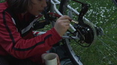 4k shot of a cute child working on lubricating the chain of his bike Stock Footage