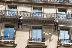 Workmen on ropes on old residential building front, Paris. Stock Photos