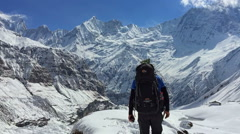 Hiker walking in Annapurna mountain valley. Snow peak Nepal Himalayas HD video - stock footage