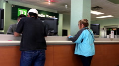 People at a bank counter talking to the teller inside TD Bank with 4k resolution - stock footage