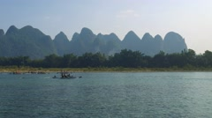 Bamboo rafts flowing through the idyllic rural landscape of Yangshuo Stock Footage