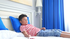 Child with remote controller lying on a bed and sleeping 2 Stock Footage