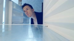 Young man sleepily opens an empty fridge and looking sad Stock Footage
