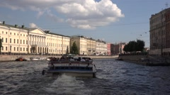 Boat rides along the Fontanka River heading to the bridge with horse statues Stock Footage