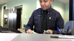 Motion of bank teller counting money for customer inside TD Bank Stock Footage