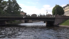 A boat turning from the Fontanka River to the Moyka River, riding under bridges Stock Footage