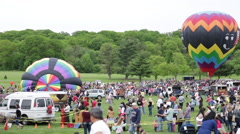 Hot Air Balloon inflating in the middle of a large crowd at a Festival Stock Footage