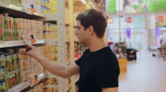 Young man chooses canned food in the store Stock Footage