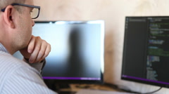 Male programmer looking for errors in the program code. Stock Footage