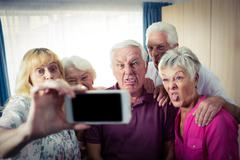 Group of seniors doing a selfie with a smartphone and funny faces Stock Photos
