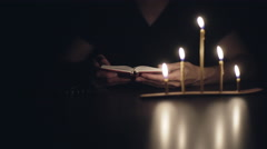 Unrecognizable human prays at night Stock Footage