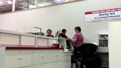 People picking up their digital hearing system inside Costco. - stock footage