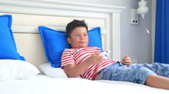 Child with remote controller lying on a bed and sleeping Stock Footage