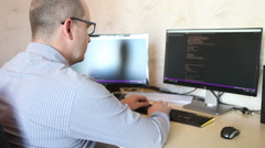 Freelance programmer working on software code sitting at the computer. Stock Footage