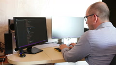 Male programmer fixes the code sitting at the computer. side view Stock Footage
