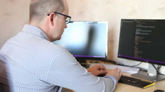 Programmer man wearily third person sitting at a computer Stock Footage