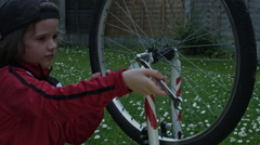 4k shot of a cute child working on unscrewing nuts on bike - stock footage