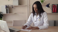 Doctor writing prescription check information on the computer Stock Footage