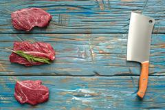 Fresh raw meat with knife on blue background. top-view Stock Photos