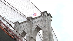 Looking up at Brooklyn Bridge with American Flag 4k Stock Footage