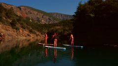 Aerial of tourists paddle boarding in river Stock Footage