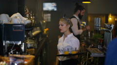 4K Bar staff serving drinks & customers chatting in city bar Stock Footage
